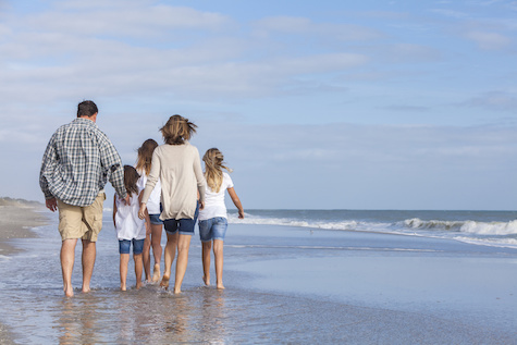 Picture of family walking on beach; parents with 3 children