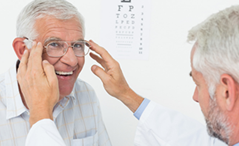 doctor fitting eyeglasses on patient's face