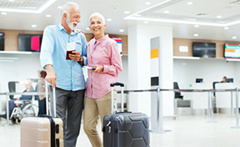 Senior couple standing in airport with luggage