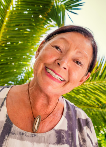 senior lady in front of palm tree