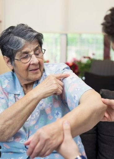 senior lady holding elbow at doctor