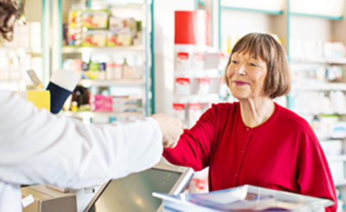 Customer receiving medication from pharmacist