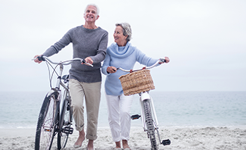 couple walking down beach with their bicycles
