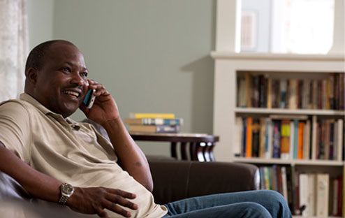 African American man happily talking on the phone in living room