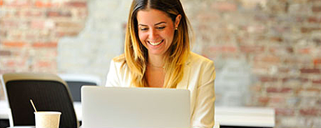 Smiling woman using computer to access her Florida Blue agent account